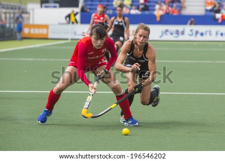 THE HAGUE, NETHERLANDS - JUNE 2: New Zealander Webster is trying to take the ball from Korean Lee during the Hockey World Cup 2014 in the  match between Korea and New Zealand. KOR beats NZL 1-0