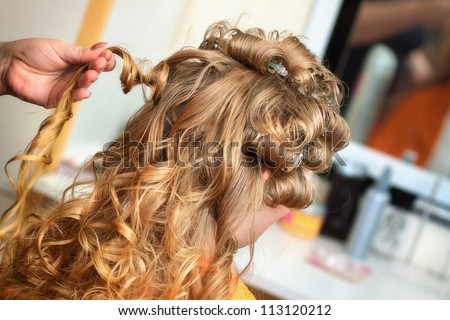 The hairdresser does a hairstyle to the bride - stock photo