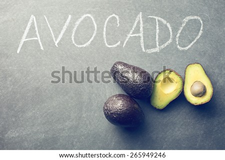 the halved avocado on blackboard - stock photo