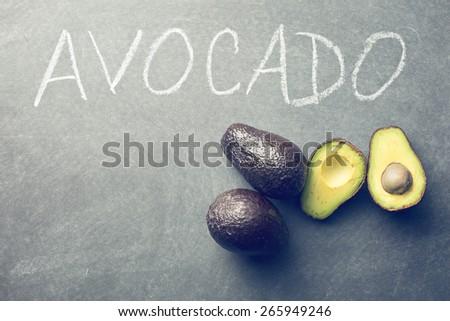 the halved avocado on blackboard - stock photo