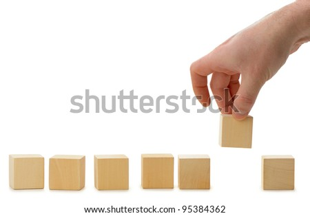 The hand establishes a wooden cube in row. It is isolated on a white background