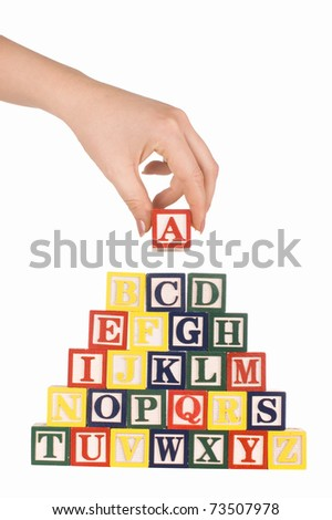 The hand holds a cube with letters - stock photo