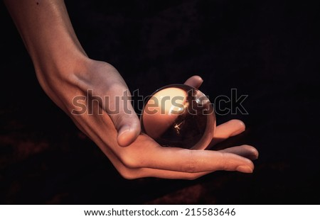 The hand holds a glass sphere - stock photo