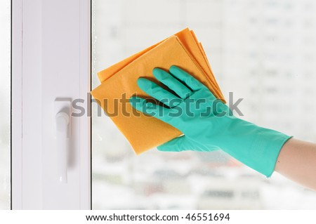 The hand in a green glove washes a window