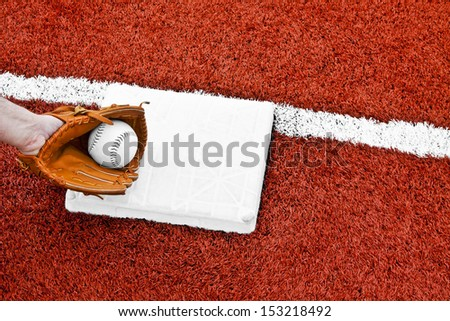 The hand in the mitt has the softball and tagging the base to put the runner out before reaching the base in the middle of the red artificial turf. - stock photo