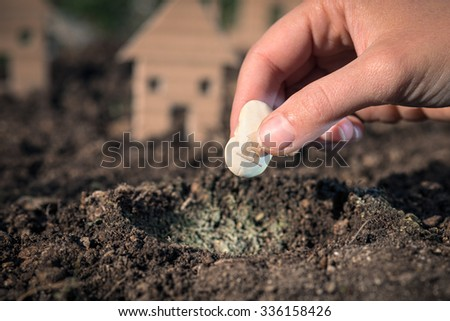 The hand is planting the seed of the house, saving concept, Italy