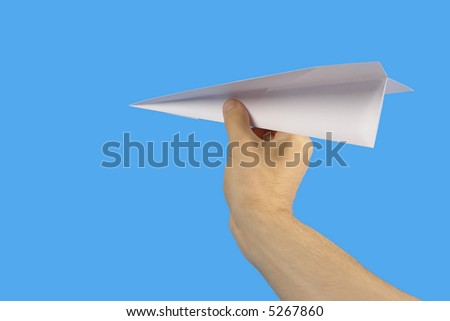 The Hand, keeping paper plane, on turn blue the background. - stock photo