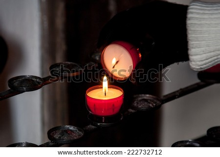 The hand lights the small candle