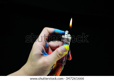 The hand mess up colorful.Hand with lighter.on black background. - stock photo
