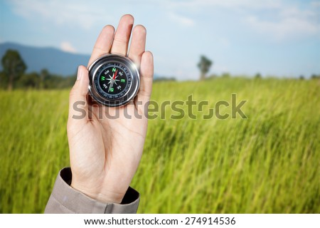 The hand of a man holding a magnetic compass over a landscape view - stock photo