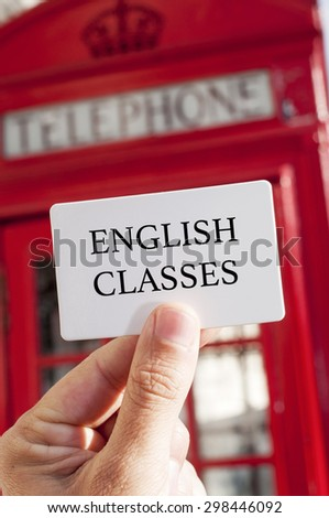 the hand of a man holding a signboard with the text english classes written in it, with a typical red telephone booth in the background - stock photo