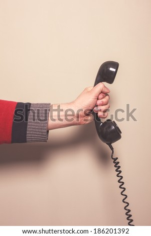 The hand of a man is holding a retro telephone receiver