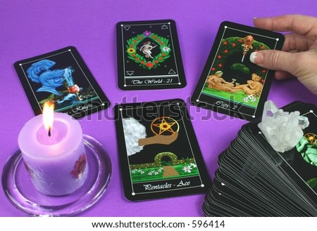 The hand of a reader laying out a tarot reading (with candle and deck in foreground)