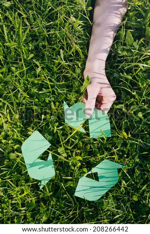 The hand of a woman adds an arrow to a green recycle sign over spring grass.