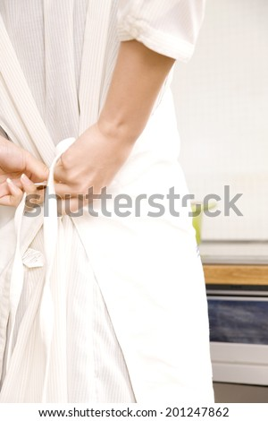 The hand of a woman wearing an apron