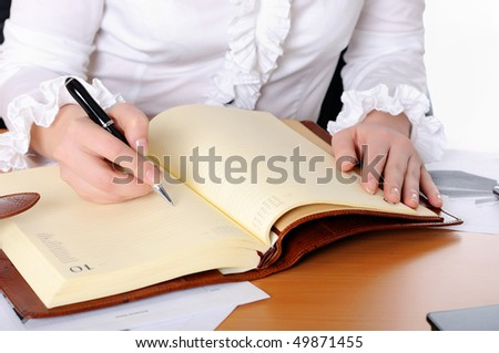 The hand of a young girl holding a black pen. Workplace business woman.