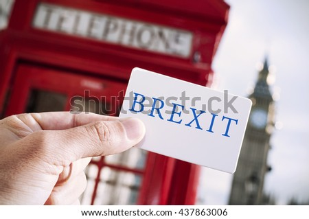 the hand of a young man showing a signboard with the text Brexit with a red telephone booth and the Big Ben in the background, in London, UK - stock photo