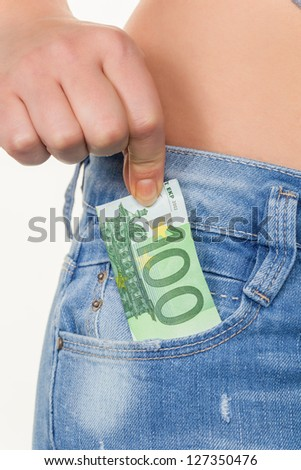 the hand of a young woman pulling a euro note from the pocket of her jeans