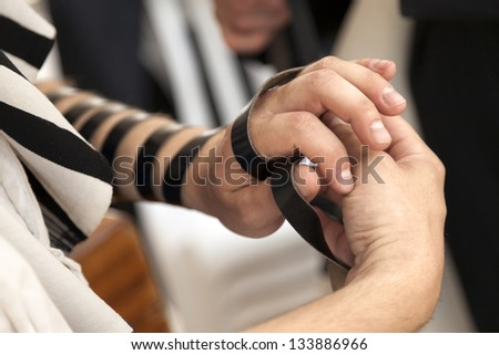 The hand of an adult Caucasian man is being wrapped in a leather strap, part of the Jewish phylacteries (Teffilin, Tefilin, Tfilin) wearing ceremony and prayer. - stock photo
