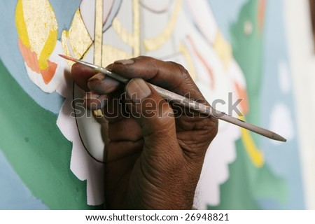The hand of an Indian artist painting a Hindu God with a squirrel hair brush - stock photo