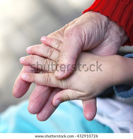 the hand of the boy and the grandmother