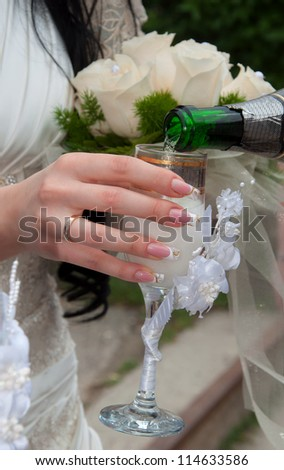 The hand of the bride with manicure  holds a beautiful glass with champagne