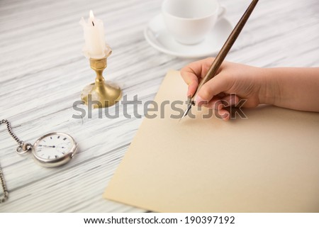 The hand of the girl writes with the ancient handle on paper - stock photo
