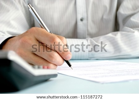 the hand of the man does entries in official papers - stock photo