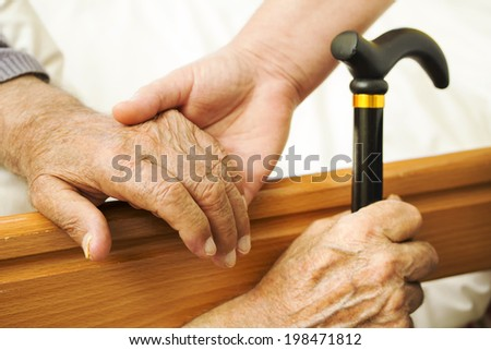 The hand of the old man and his daughter in the fifties, next to the hospital bed. Focus on an old hand.  - stock photo