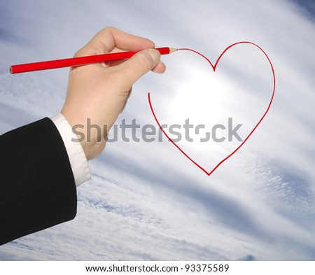The hand of the person in a business suit draws a heart sign