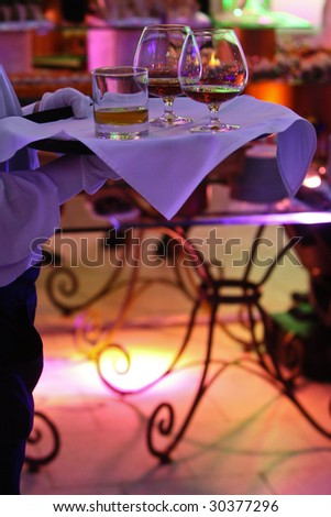 The hand of the waiter holds a tray with glasses on a buffet table. A changing color light-emitting diode illumination of facility.