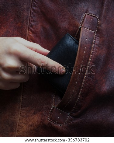 The hand of the white man pulls out a wallet from another's pocket. The concept of stealing money, crime - stock photo