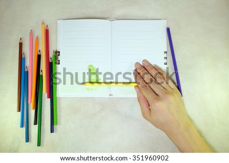 The Hand On Colorful pencils and note.on the mulberry paper cream tone. - stock photo