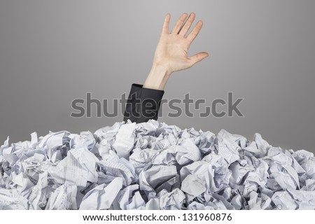 The hand reaches out from big heap of crumpled papers