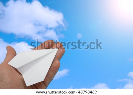 The hand starting paper planes in the sky. - stock photo