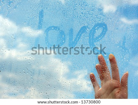The hand writes on wet glass on a background of clouds