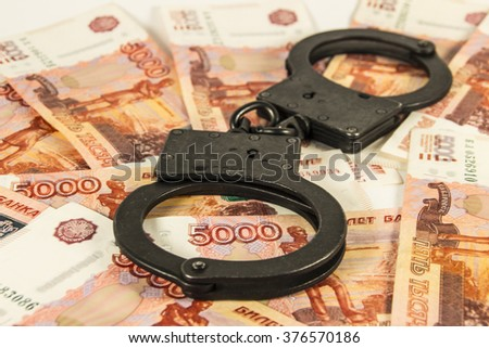 The handcuffs on the background of the Russian ruble - stock photo
