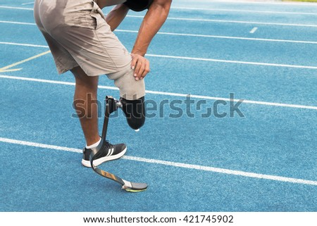 The handicapped runner with prosthetic leg taking a break on the track during workout