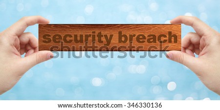 The Hands holding a wood engrave with word security breach with bokeh background - stock photo