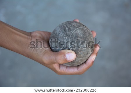 The hands of a man holding Petanque (boule) balls. - stock photo