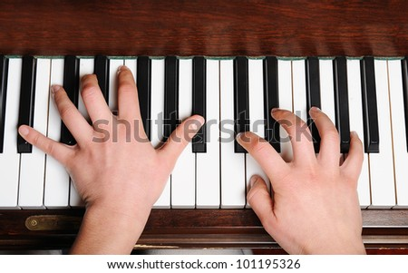 the hands of a pianist in action on piano in a plan - stock photo