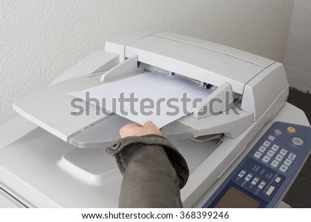 The hands of a young businesswoman is placing a document to copy it - stock photo
