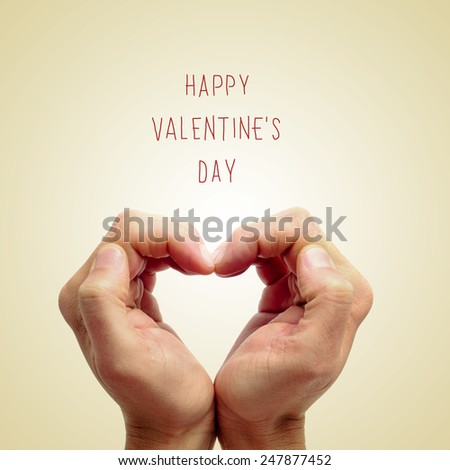 the hands of a young man forming a heart and the sentence happy valentines day written on a beige background - stock photo