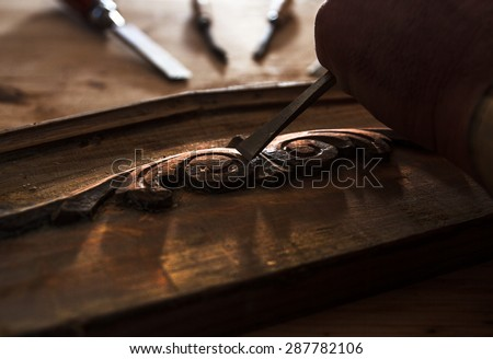 The hands of an carpenter restoring old furniture with chisel, Close up. Dark color intensity. - stock photo