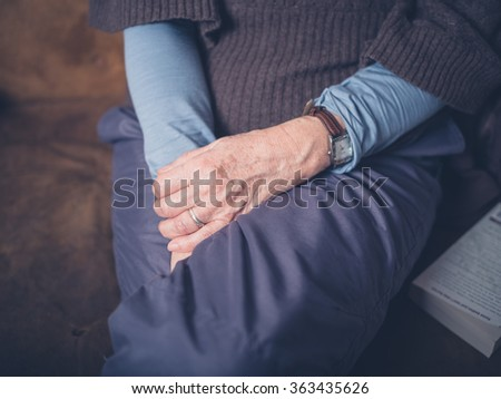 The hands of an elderly woman relaxing on a sofa at home
