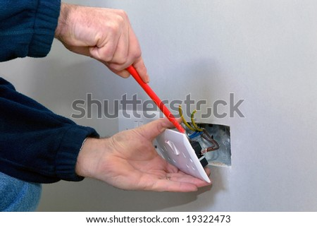The hands of an electrician installing a power socket - stock photo