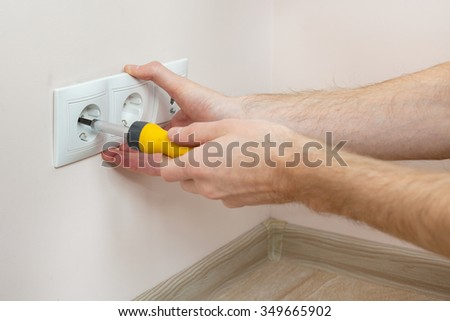 The hands of an electrician installing a wall power socket with screwdriver - stock photo
