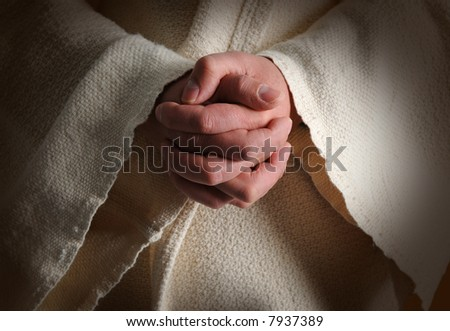 The hands of Jesus clasped in prayer - stock photo