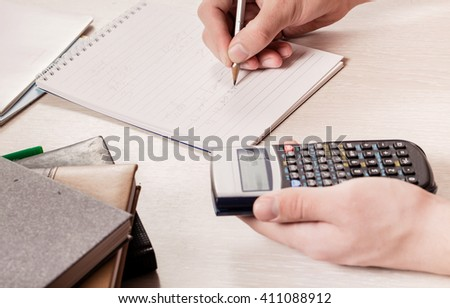 The hands of the person holding the calculator and a pencil. Calculation of people writes down results in a notebook. Close up - stock photo