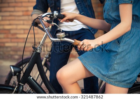 The hands of young couple sitting on bicycles opposite the city